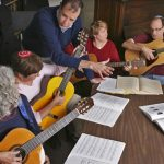 Academy for Jewish Religion. Students with guitars sit around a table looking at sheet music.