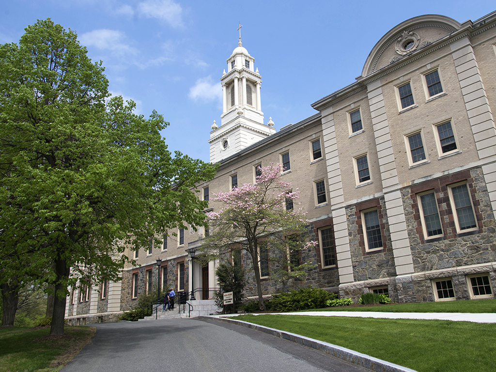 Boston College School of Theology and Ministry. A gray academic building with some trees in front.