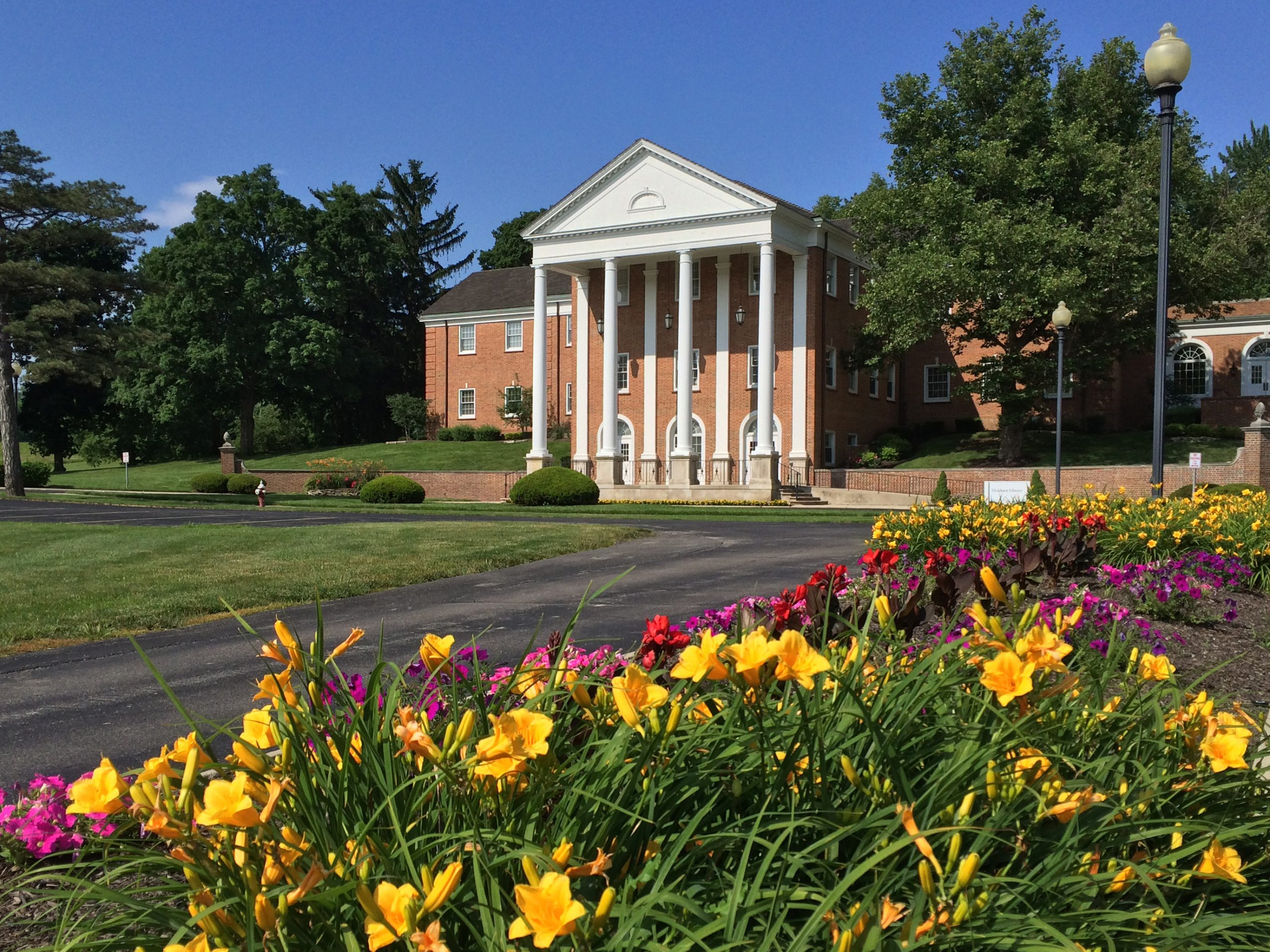 Methodist Theological School in Ohio. Distant academic building surrounded by green trees. A flower garden sits closer to the camera.